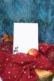 Guantes calientes de Borgoña con una bufanda y un sombrero en color de fondo azul de madera con las hojas de otoño, y reducido un Imagen de archivo