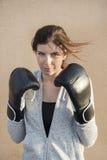 Guantes de boxeo de la mujer que llevan confiada fotografía de archivo