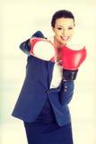 Guantes de boxeo jovenes de la mujer de negocios que desgastan Foto de archivo libre de regalías