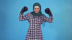 Guantes de boxeo de la mujer que llevan musulmán joven confiada en el fondo azul que mira la cámara almacen de metraje de vídeo