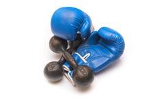 Guantes de boxeo y pesa de gimnasia oxidada en un fondo blanco Imágenes de archivo libres de regalías