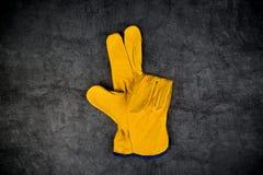 Guantes de cuero de la construcción que hacen tres fingeres Gest Foto de archivo libre de regalías