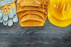 Guantes de cuero de la seguridad del casco de la correa de la herramienta en el tablero de madera Imágenes de archivo libres de regalías
