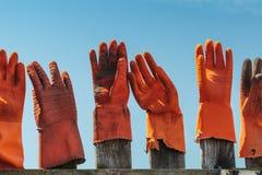 Guantes de goma anaranjados en una cerca de madera Foto de archivo