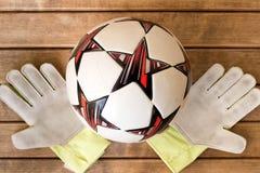 Guantes de la bola y del portero de fútbol en fondo de madera Foto de archivo