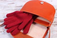 Guantes de lana con el bolso de cuero abierto para la mujer en viejo fondo de madera Imágenes de archivo libres de regalías