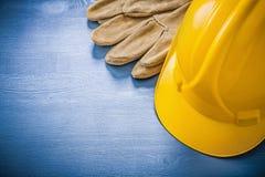 Guantes de trabajo que construyen el casco en el concep de madera de la construcción del tablero Fotografía de archivo