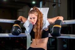 Guantes del deporte de la muchacha que llevan que se sientan en la esquina del ring de boxeo Fotos de archivo