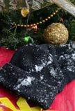 Guantes del punto del negro del invierno y sombrero caliente en una nieve Fotos de archivo libres de regalías