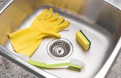 Guantes, esponja y cepillo en un fregadero de cocina limpio Imagen de archivo