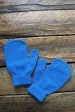 Guantes o manoplas azules del invierno en un fondo de madera aislado Imagen de archivo