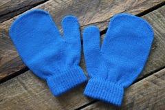 Guantes o manoplas azules del invierno en un fondo de madera aislado Fotos de archivo