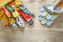 Guantes protectores de la correa de la herramienta de los útiles de la construcción en el tablero de madera Fotografía de archivo