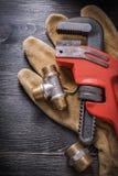 Guantes protectores de los accesorios de fontanería de la llave inglesa Imagen de archivo