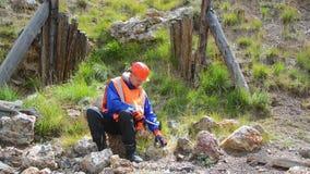 Guantes que llevan de minas de un ingeniero o del geólogo, un casco, un chaleco reflexivo almacen de video