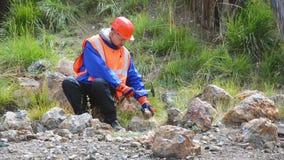 Guantes que llevan de minas de un ingeniero o del geólogo, un casco, un chaleco reflexivo metrajes