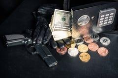Guantes y arma por la caja fuerte abierta con el bitcoin imágenes de archivo libres de regalías