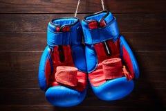 Guantes y vendaje azules y rojos de boxeo en fondo marrón del tablón Fotos de archivo libres de regalías