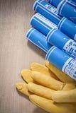 Guanti blu di sicurezza dei disegni di ingegneria sul construc del bordo di legno Fotografie Stock Libere da Diritti