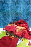 Guanti caldi di Borgogna con una sciarpa e un cappello su colore blu del fondo di legno con le foglie di autunno e tagliato un al Fotografia Stock Libera da Diritti