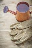 Guanti d'annata di sicurezza dell'annaffiatoio su agricoltura c del bordo di legno Fotografia Stock Libera da Diritti