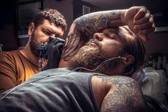 Guanti d'uso dell'uomo che posano nel salone di tatoo Fotografie Stock