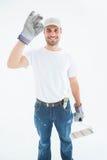 Guanti d'uso dell'uomo felice mentre tenendo il rullo di pittura Immagine Stock Libera da Diritti