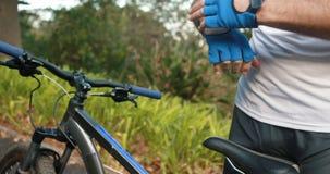 Guanti d'uso di sport del ciclista maschio in foresta video d archivio