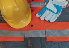 Guanti del casco messi su vestiario di protezione per lavoro fotografia stock
