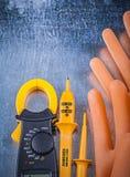Guanti di gomma degli elettricisti elettrotecnici del tester dell'amperometro di Digital sopra immagini stock