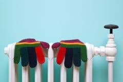 Guanti di lana a strisce sul vecchio radiatore Fotografia Stock