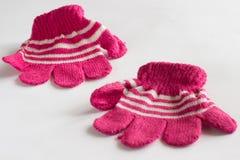 Guanti di rosa di bambino su un bianco Fotografia Stock