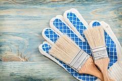 Guanti di sicurezza dei pennelli sul concetto della costruzione del bordo di legno Fotografia Stock