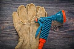 Guanti di sicurezza del cuoio della pistola del giardino su agricoltura del bordo di legno Immagini Stock Libere da Diritti