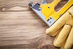 Guanti di sicurezza della pistola della cucitrice meccanica sul concetto di legno della costruzione del bordo Immagini Stock