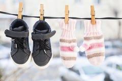 Guanti e scarpe rosa di un bambino che appende sulla molletta da bucato Fotografia Stock