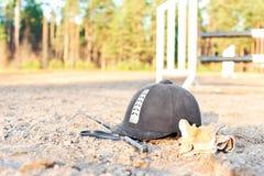 Guanti equestri e frusta del casco dimenticati sulla terra Fotografie Stock
