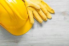 Guanti gialli di sicurezza del cuoio del casco sul constructi del bordo di legno Fotografie Stock