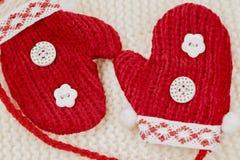 Guanti miniatura rossi sul cappuccio tricottato bianco Immagine Stock