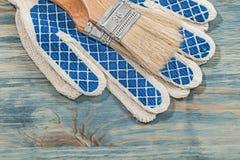 Guanti protettivi dei pennelli sulla costruzione del bordo di legno concentrata Fotografia Stock Libera da Diritti