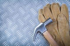 Guanti protettivi del cuoio del martello da carpentiere sul fondo scanalato in del metallo Immagine Stock Libera da Diritti