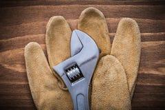 Guanti protettivi del cuoio della chiave regolabile sul raggiro del bordo di legno Fotografia Stock Libera da Diritti