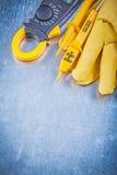 Guanti protettivi del tester elettrico dell'amperometro di Digital su metallo immagini stock libere da diritti