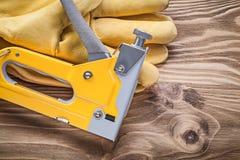 Guanti protettivi della pistola della cucitrice meccanica sul concetto di legno della costruzione del bordo Fotografie Stock