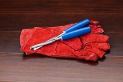 Guanti rossi e scalpelli blu sul pavimento di legno Fotografia Stock Libera da Diritti