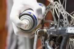 Guanto bianco d'uso della mano del primo piano facendo uso dello spruzzo del grasso sulle parti della ruota di bicicletta, concet Fotografia Stock Libera da Diritti