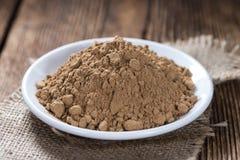 Guarana Powder. Portion of Guarana Powder on dark wooden background stock photo