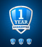 Guarantee label shield on blue background. With warranty labels Royalty Free Stock Photos
