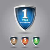 Guarantee label shield on grey background Stock Images