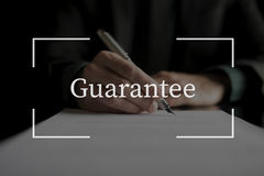 Guarantee text over conceptual business scene. With businessman signing a contract, placed on black desk Royalty Free Stock Photo